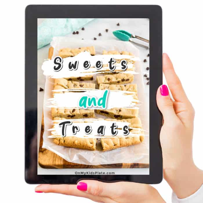Hands hold an ipad with the Sweets and Treats ecookbook on the cover