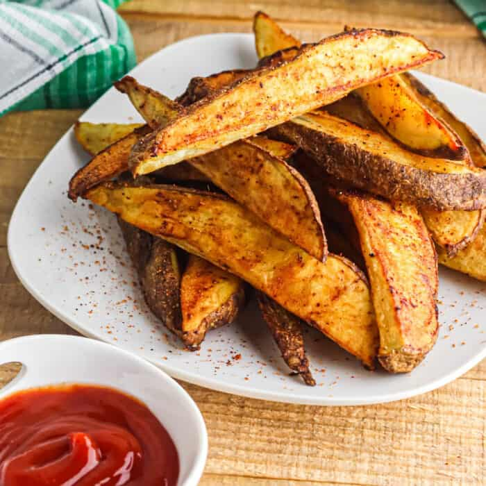 A plate full of crispy potato wedges next to a small cup of ketchup and a napkin.