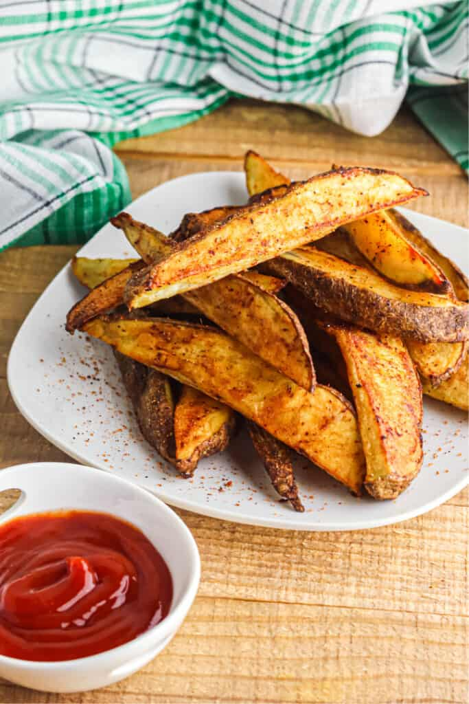 Potato wedges piled high on a plate next to a bowl of ketchup and a napkin