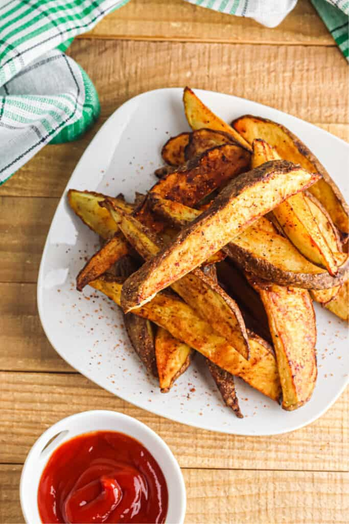 Overhead view of roasted potato wedges on a plate next to a cup of ketchup and a kitchen linen.
