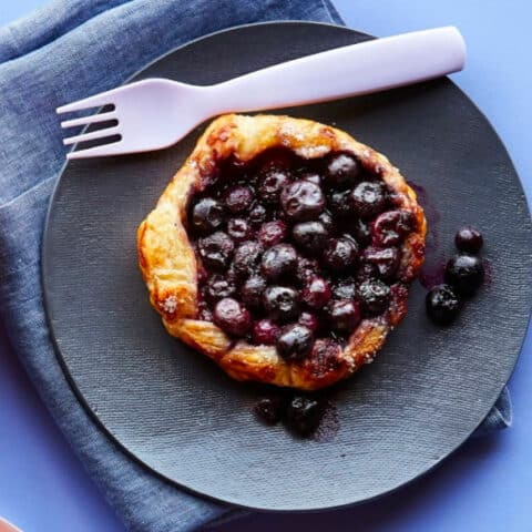 A blueberry galette on it's own plate with a fork and napkin
