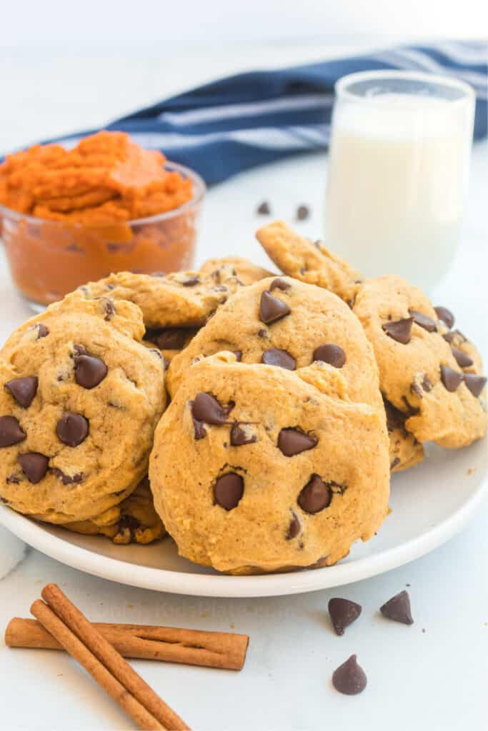 Cookies with chocolate chips piled on a plate with a bowl of pumpkin puree and a glass of milk behind the plate, and cinnamon sticks in front of the plate