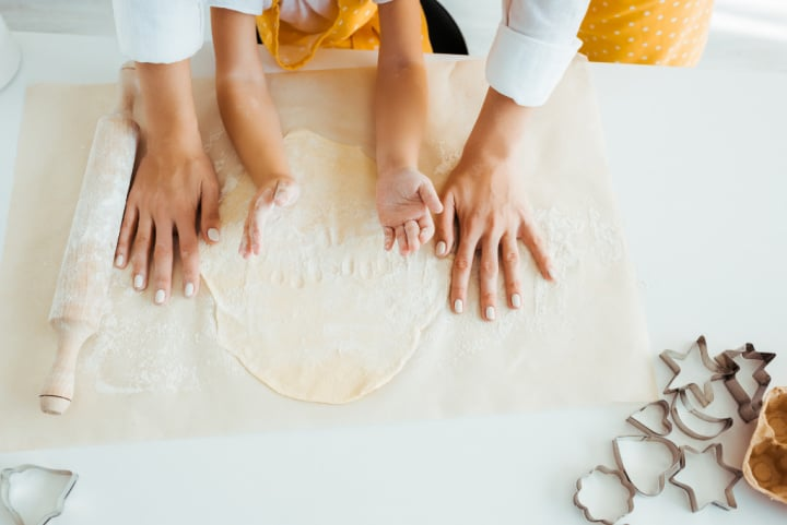 child and adult hands rolling dough on paper with cookie cutters nearby