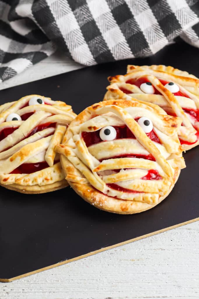 round cherry hand pies that have been baked and decorated to look like mummy faces