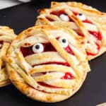 Close up of two cherry hand pies decorated like mummies