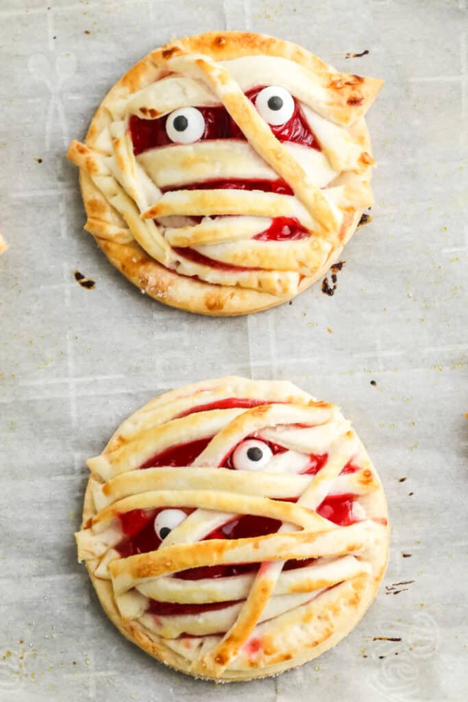 Finished mummy hand pie on the pan with candy eyes