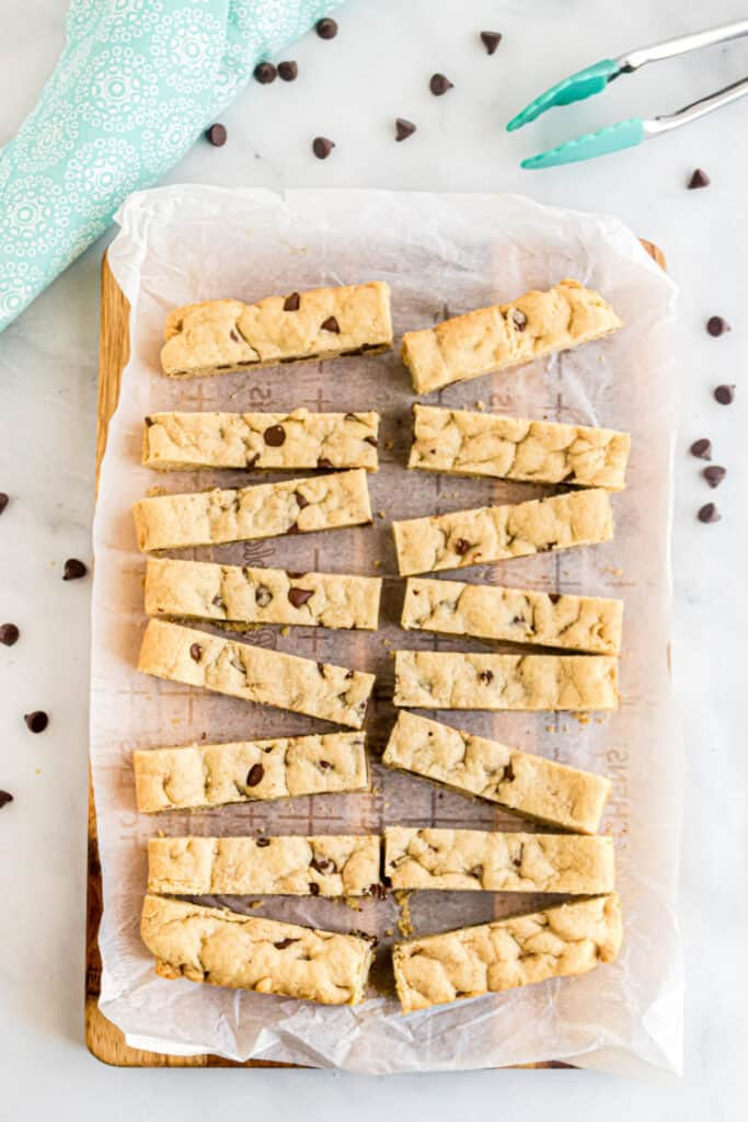 Chocolate chip cookie sticks cut into thin slices on a cutting board.