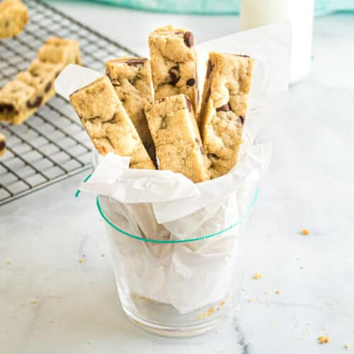 Chocolate cookie sticks served in a glass lined with parchment paper.