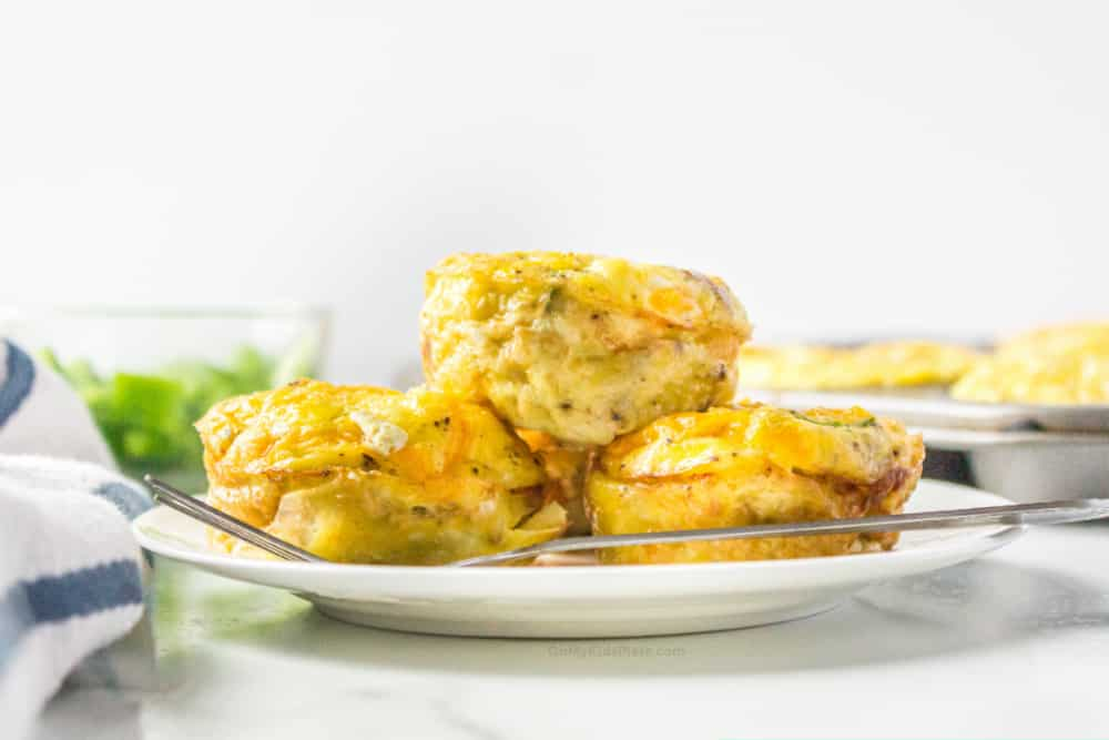 Three egg muffins stacked on a plate from the side with a muffin pan behind