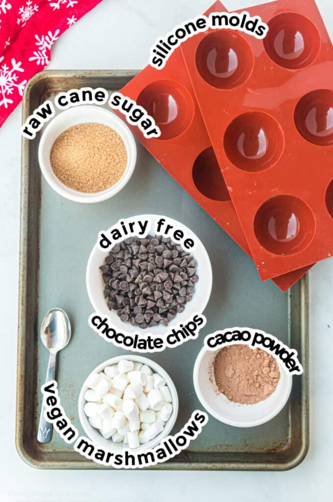 Ingredients for dairy free hot cocoa bombs on a baking sheet.