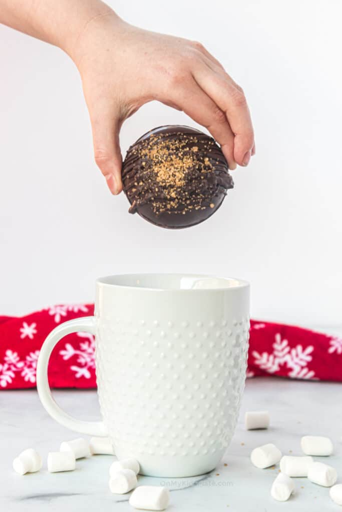Child's hand placing a hot cocoa bomb into a mug