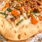 Close up of pizza with squash, greenbeans, stuffing and turkey