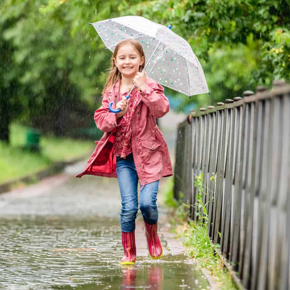 Little girl jumps laughing in spring puddles with an umbrella