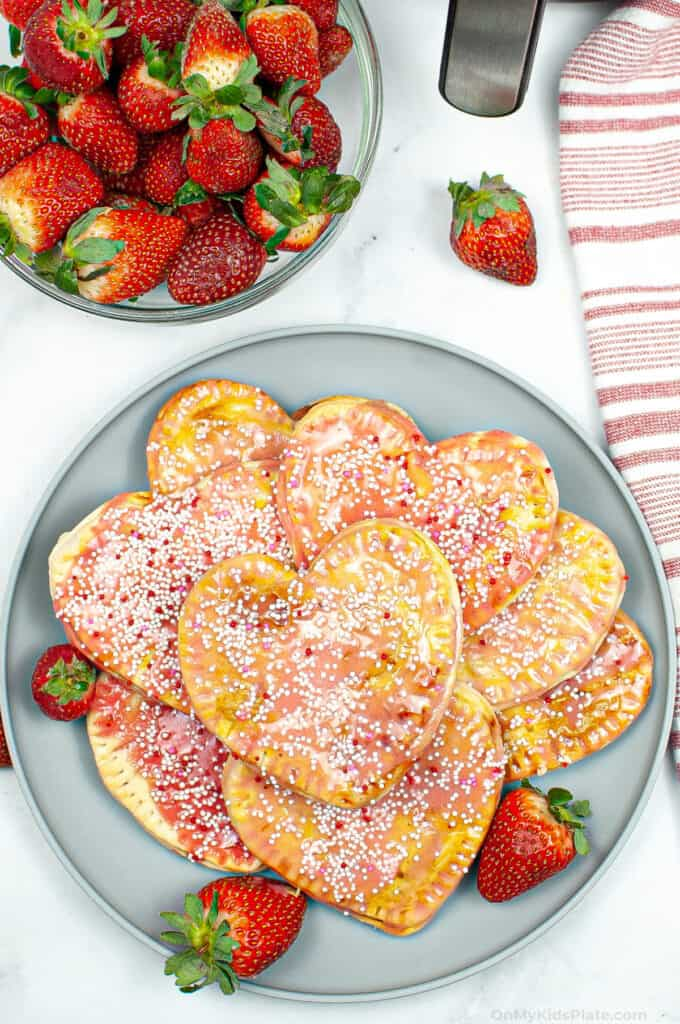 A platter of strawberry pop tarts from overhead with a bowl of strawberries