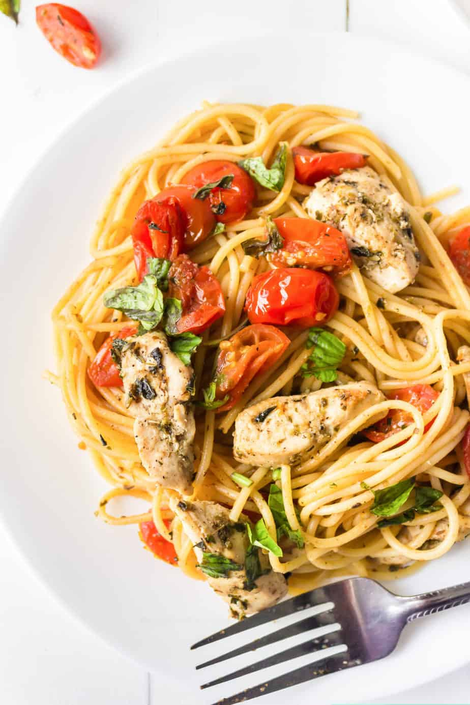 Up close of a plate with tomatoes, thin spaghetti, chicken and basil to make chicken bruschetta pasta.