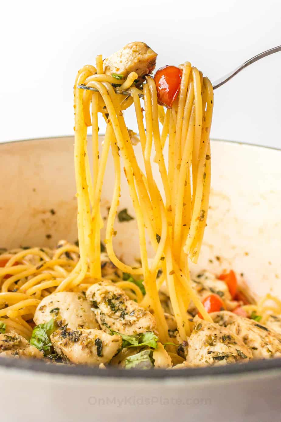 Side view of long pasta, chicken and tomatoes being lifted out of the pot with a fork.