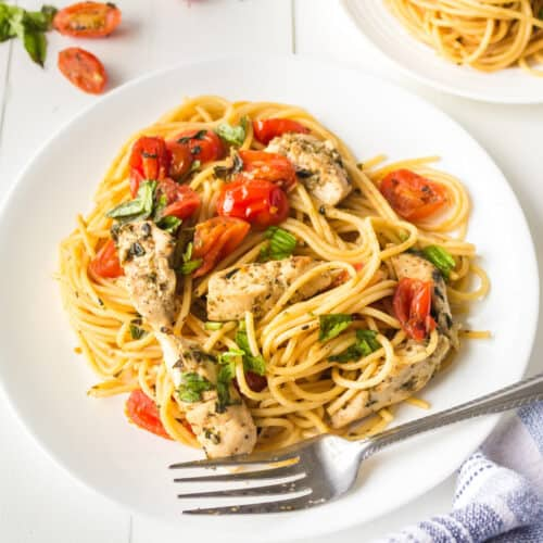 Up close plate of bruschetta chicken pasta with tomatoes, basil and an extra plate of spaghetti also at the table.