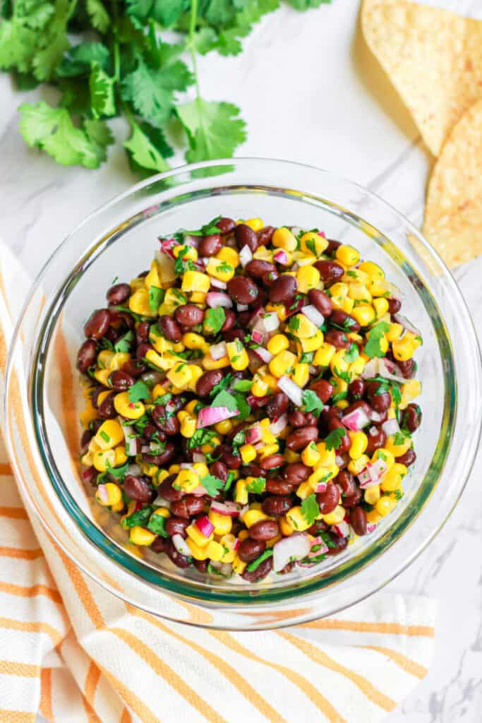 Black bean corn salsa in a bowl with chips and cilantro on the counter