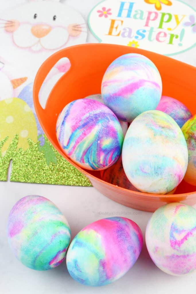 Marbled dyed colorful Easter Eggs in a basket and in front of the basket.