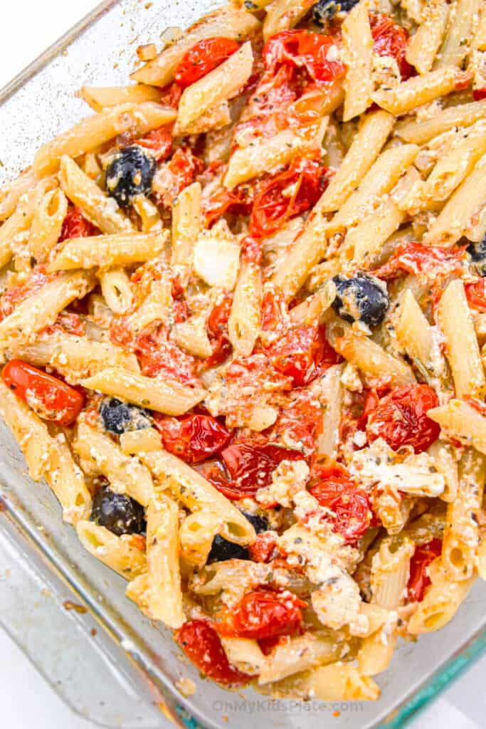 Penne pasta with roasted tomatoes, olives and feta cheese mixed in a casserole dish.