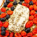 feta in a baking pan with roasted tomatoes and olives
