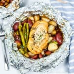 An open foil packet from the grill with chicken, potatoes and asparagus cooked inside