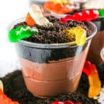 Up close of chocolate pudding in a clear cup layered with chocolate cookie crumbs and gummy worms to look like dirt.