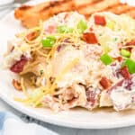 potato salad topped with cheese, green onions and bacon on a dinner plate with chicken behind